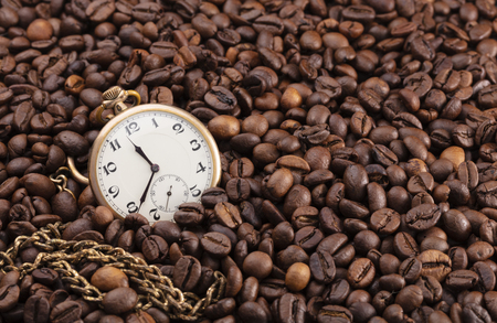 old pocket watch, golden, with a long chain on a pile of coffee beans, conceptual photo showing that any time is good for a coffee 免版税图像