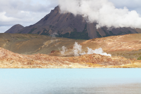 blue geothermal lake in volcanic zone with the cone of a volcano in the background, there are steam fumaroles 免版税图像