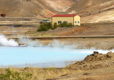 geothermal station with the red roof, producing electricity with a turquoise lake in front and steam pipes