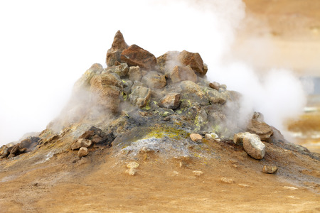 volcanic fumarole emitting gas, sulphur is seen between the pile of rocks on a brown soil