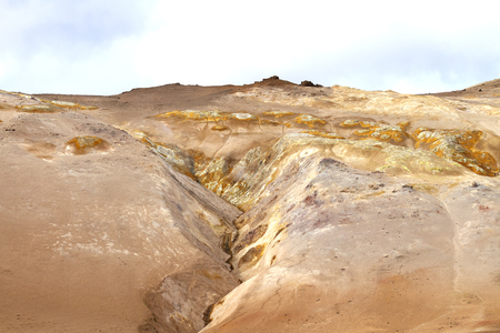 volcanic landscape in iceland, hills of sand, cracks and solidified lava under a gray sky