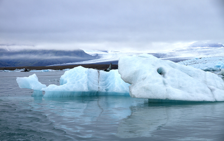 piece of blue ice of a glacier floating on the water with the mountains and the glacier in the background Banco de Imagens
