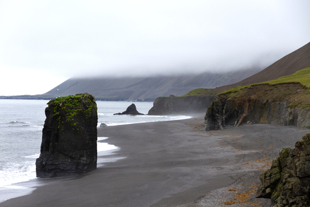 volcanic black sand beach in iceland with a large rock and cliffs