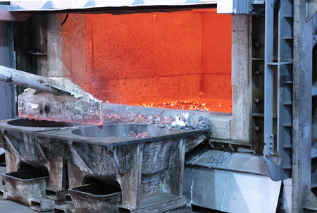 skimming melted aluminum for removing the dross before casting. Aluminum foundry works showing an open furnace Stock fotó