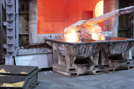 skimming melted aluminum for removing the dross before casting. Aluminum foundry works showing an open furnace 免版税图像