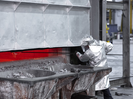 a worker taking a sample of molten aluminum from the inside of a big furnace dressing the personal protective clothing aluminized