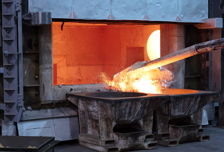 skimming melted aluminum for removing the dross before casting. Aluminum foundry works showing an open furnace Zdjęcie Seryjne