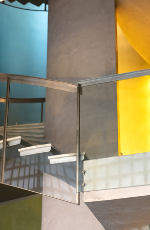 construction detail of a spiral staircase with a steel and glass railing, the walls are painted in blue , yellow and cement 免版税图像