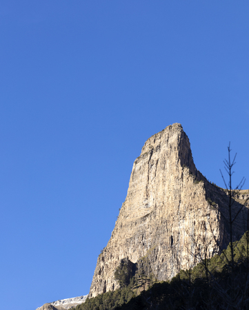 vertical wall in the Ordesa National Park in Spain over an intense blue sky, at the bottom of the wall, the forest.