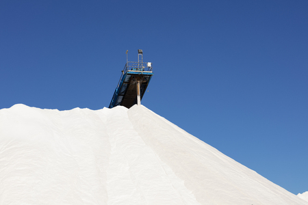 mountain of white salt on blue sky, salt extraction process and piled up
