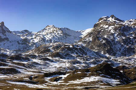 snowy mountains landscape showing the first snow on brown grass during the winter with a blue and clear sky 免版税图像