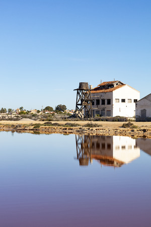 old ruined building with wooden water tank on the edge of a saline lake, both are reflected in the water on the blue background of the sky