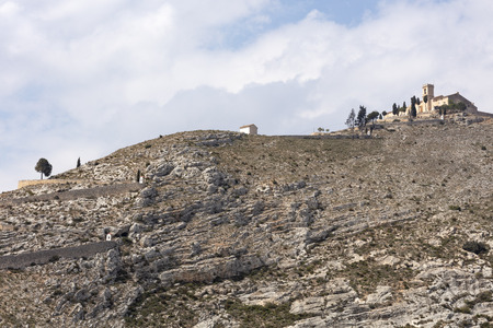 ermitage of saint christ on top of the hill in Bocairent, Spain with the pathway, the hill is rocky and the sky in the background is cloudy