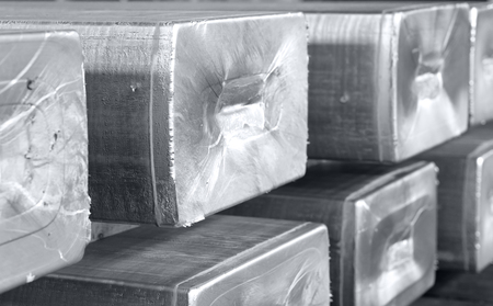 heavy aluminum ingots stacked in a warehouse foundry, raw material to be processed in a hot mill. Photo in black and white with bluish tone