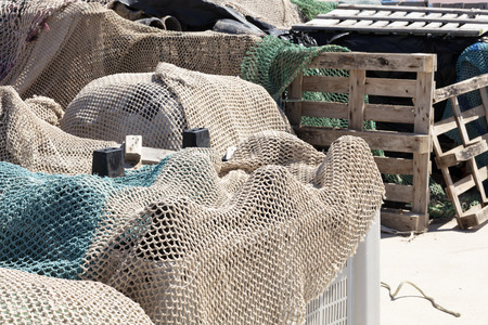 fishing nets in the port revised in plastic boxes to be used, with wooden boxes in the background 免版税图像