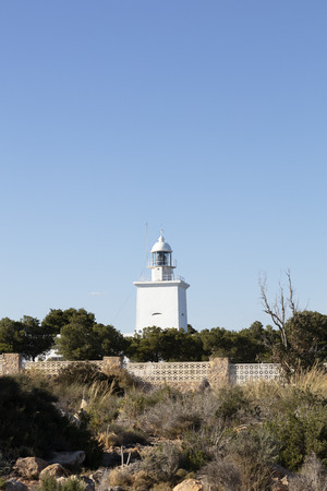 white mediterranean lighthouse of Santa Pola with the coast of Alicante in the background