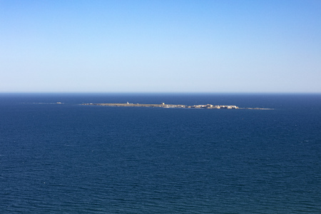 panoramic view of Tabarca island from the Santa Pola lighthouse in Alicante, Spain, on an intense blue mediterranean sea and clear sky