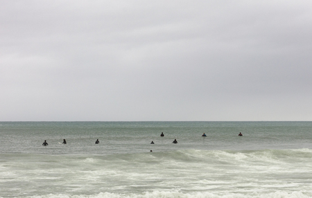 surfers on the tables waiting the wave in a winter cloudy day they wear a black neoprene suit, free space for text on top
