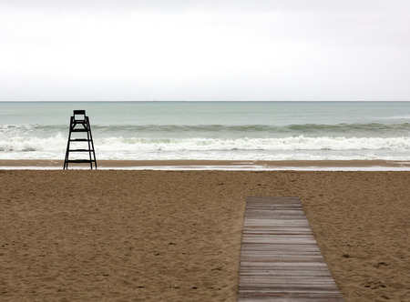the beach during a cloudy day with a beach watchman chair alone on the sand and a wooden pathway
