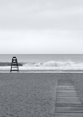 the beach during a cloudy day with a beach watchman chair alone on the sand and a wooden pathway. Black and white photo with free soace for text on top 免版税图像