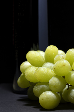 bunch of white grapes with water drops on black background with a light reflection on the bottle