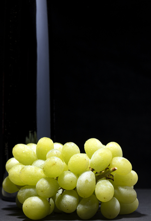 bunch of white grapes with water drops on black background with a bottle on the left, free space for text