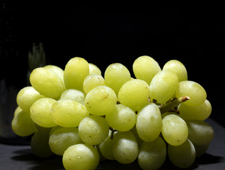 bunch of white grapes with water drops on black background