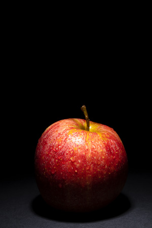 red apple with drops of water on black background, image conveys freshness, free space above for text