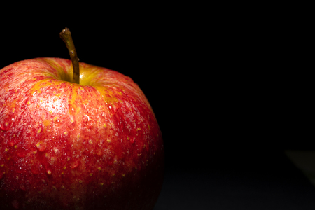 red apple with drops of water on black background, image conveys freshness, free space on the right for text