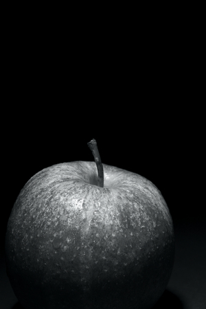 apple with drops of water on black background, image conveys freshness, black and white photography and free space above for text