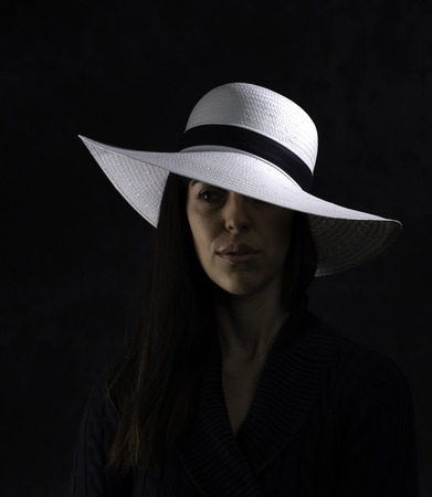 portrait of a beautiful young girl with a white hat on a black background, looking at her side