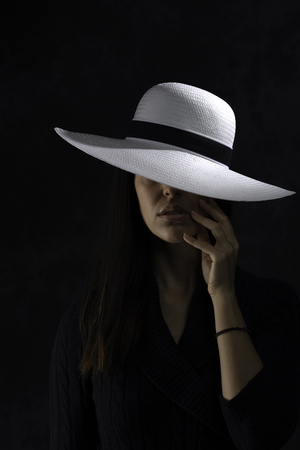 portrait of a beautiful young girl with a white hat on a black background, holding her hand under her chin