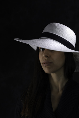 portrait of a beautiful young girl with a white hat on a black background,  looking at the camera 新闻类图片