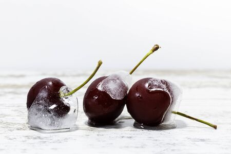 cherries frozen on wooden table with white background, free space for text on top