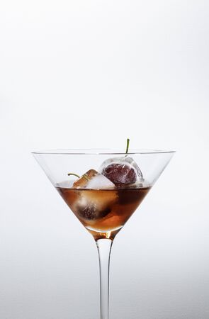 ice cubes with cherries inside into a red cocktail, white background with free space for text 免版税图像 - 132005849