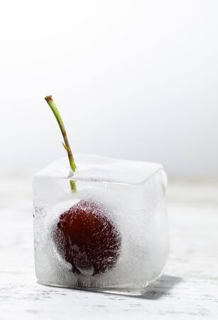 ice cube with a frozen cherry inside on a wooden table and white background