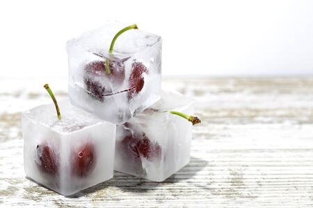 ice cubes with cherries inside on a wooden table and white background 免版税图像