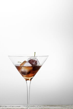 ice cubes with cherries inside into a red cocktail, white background textured with free space for text