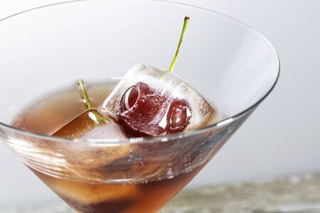 ice cubes with cherries inside into a red cocktail, white background with free space for text
