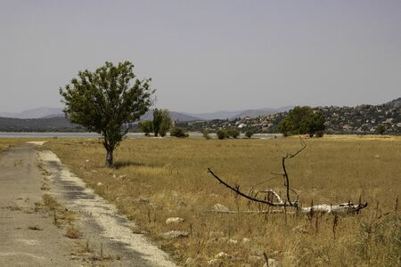 summer landscape with the Manzanares dam and Colmenar Viejo village in Madrid in the background with its castle