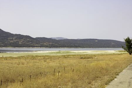 dry and sunny landscape with the Manzanares river and the forest in the background