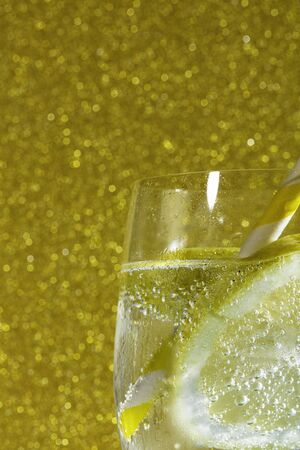 fresh soda with bubles an ice cube, a  slice of lemon and a straw on a shiny golden background, free space for text 免版税图像