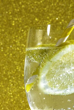 fresh soda with bubles an ice cube, a  slice of lemon and a straw on a shiny golden background