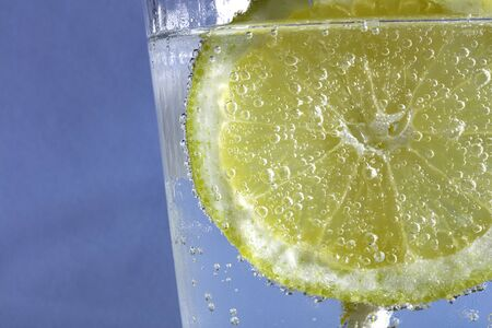 fresh drink with bubles an ice cube, a  slice of lemon and a straw on a blue background