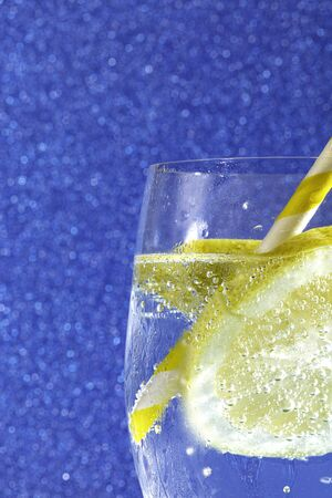 fresh soda with bubbles an ice cube, a  slice of lemon and a straw on a shiny blue background
