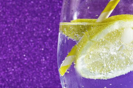 fresh soda with bubbles an ice cube, a  slice of lemon and a straw on a shiny purple background. Free space for text