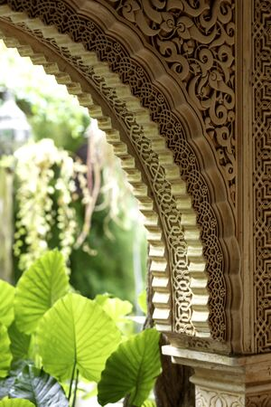 arch decorated with arabic ornaments with an interior green garden in the background Banco de Imagens