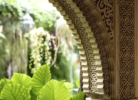 arch decorated with arabic ornaments with an interior green garden in the background 免版税图像