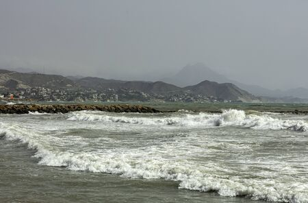 red flag on the breakwater of the beach after the storm, with the mountain coast in the background
