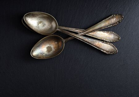 three old and worn teaspoons stacked on a slate board, free space for text 免版税图像